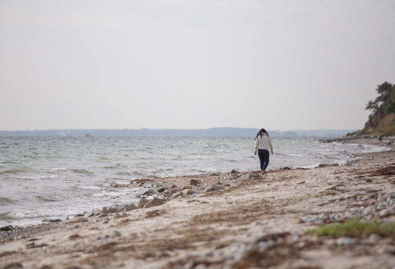lonely girl walking along the beach ©Erika's Way Photography