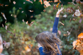 A 3.5 years old girl dancing under a rain of Autumn leaves. Photo by Erika's Way Photography