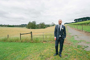 The Groom between the vines and the hay field. © Erika's Way Wedding Photography