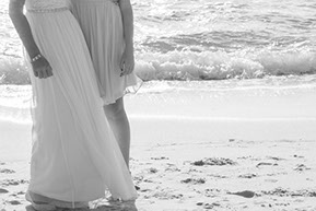 Bride and Daughter detail of the wedding dresses in the wind at the beach. Black and white photo. © Erika's Way Photography
